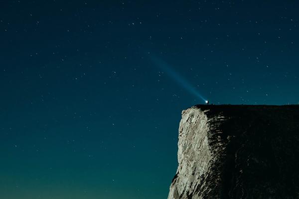 Faro su una scogliera che brilla nel cielo notturno