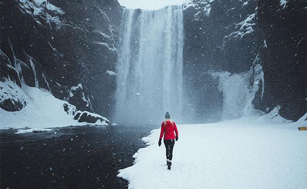 Donna che cammina nella neve diretta verso una cascata